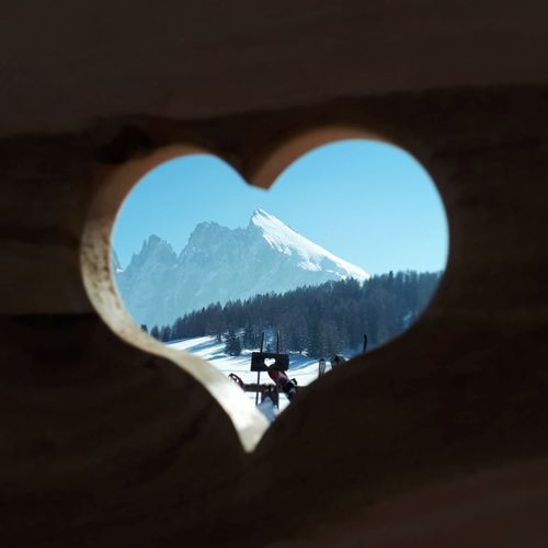 Scenic view of snowcapped mountains seen through heart shaped hole