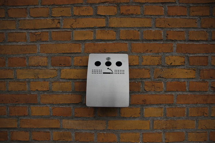 Silver cigarette dustbin mounted on brick wall