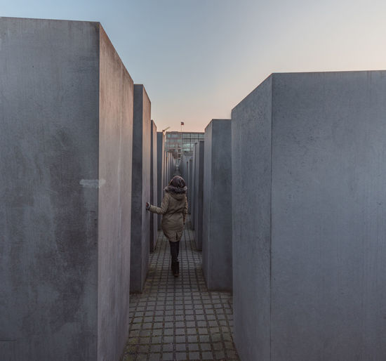 Rear view of man standing amidst holocaust memorial against sky