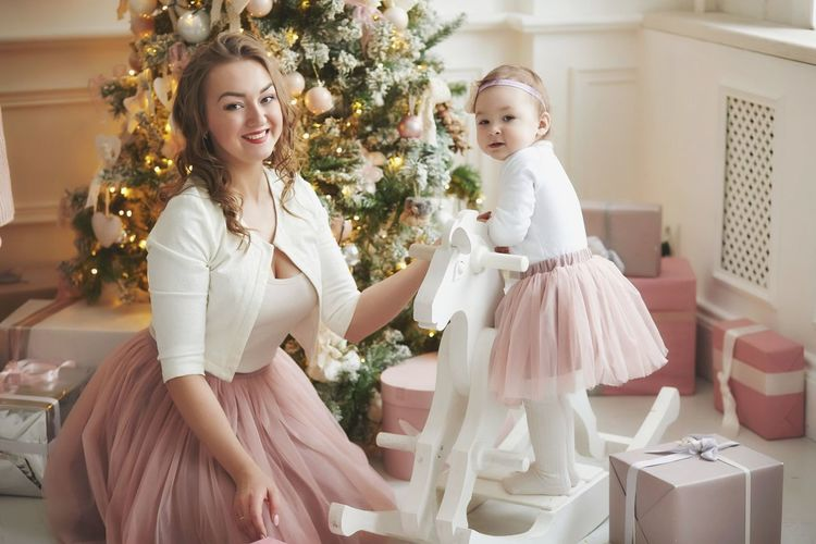 Portrait of smiling mother and daughter against christmas tree