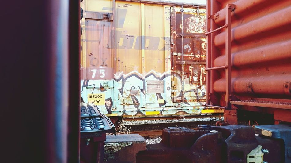 EyeEm Selects Trains Day No People Corrugated Iron Close-up Looking Through Graffiti Metal Freight Train Train Cars Train Yard Freight Transportation Business Finance And Industry Architecture Rust Machinery Equipment The EyeEm Collection