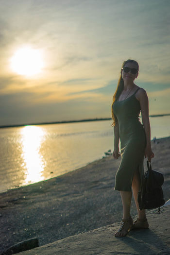 Full length portrait of young woman standing at beach during sunset
