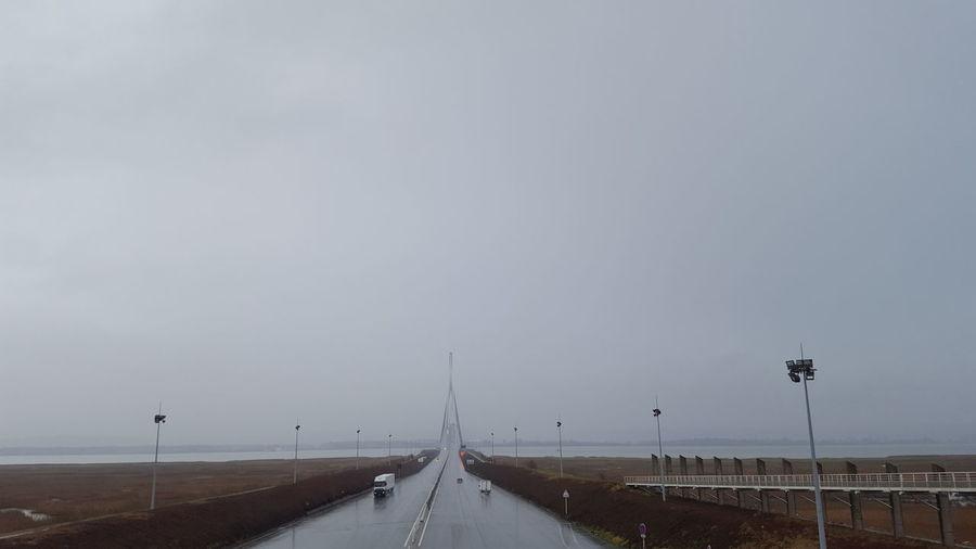 Road by bridge against sky