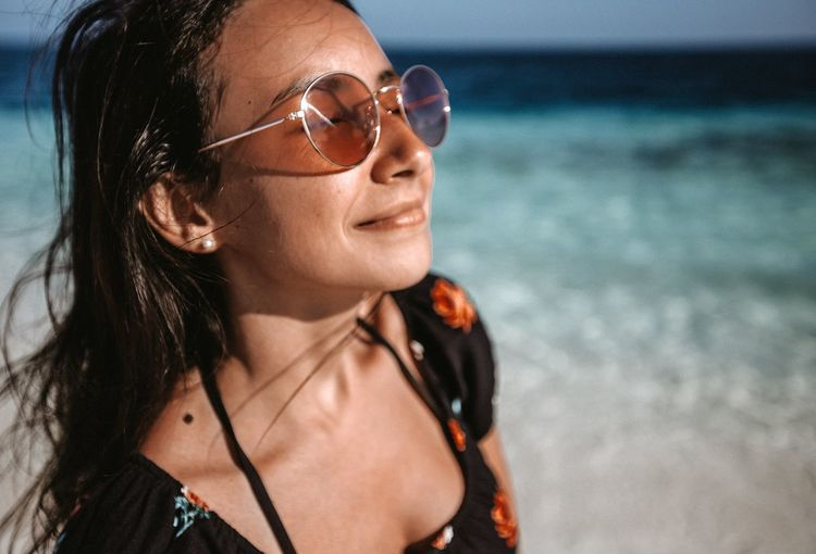 Close-up of young woman wearing sunglasses at beach