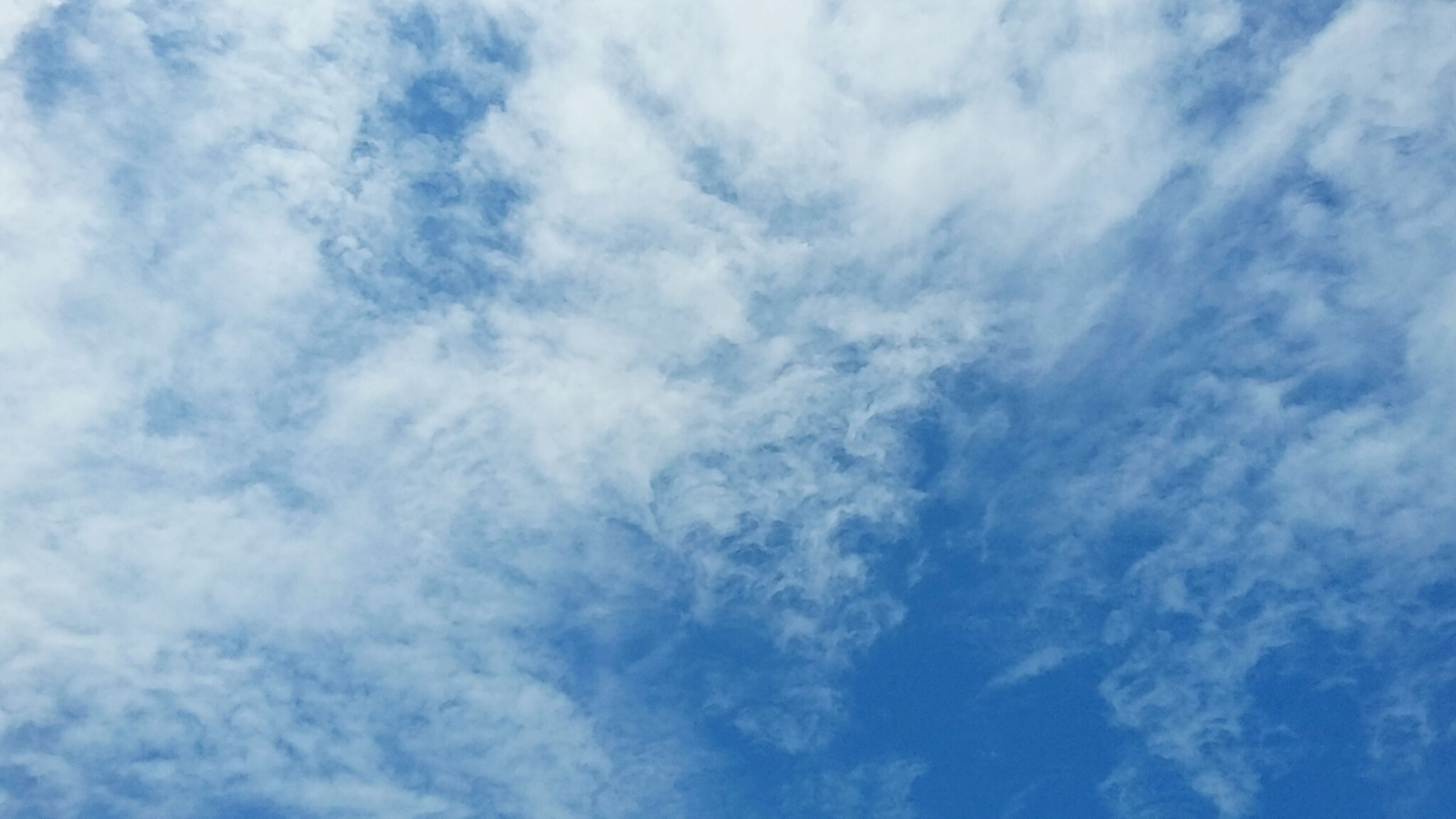 sky, low angle view, cloud - sky, backgrounds, sky only, beauty in nature, full frame, tranquility, blue, scenics, cloudy, nature, tranquil scene, cloudscape, cloud, idyllic, white color, day, outdoors, no people