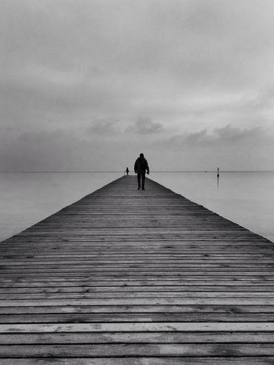 Man Walking On Jetty Against Seascape