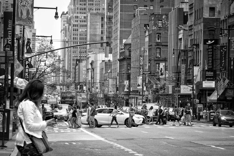 People crossing street against buildings in city