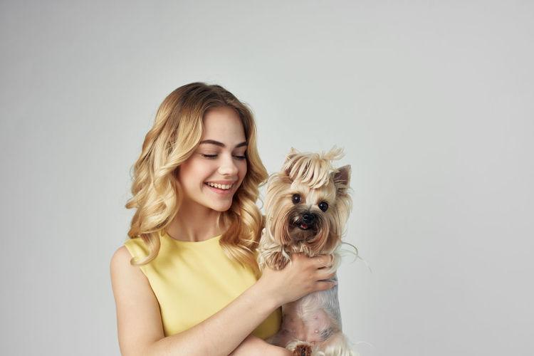 Portrait of teenage girl holding dog against white background