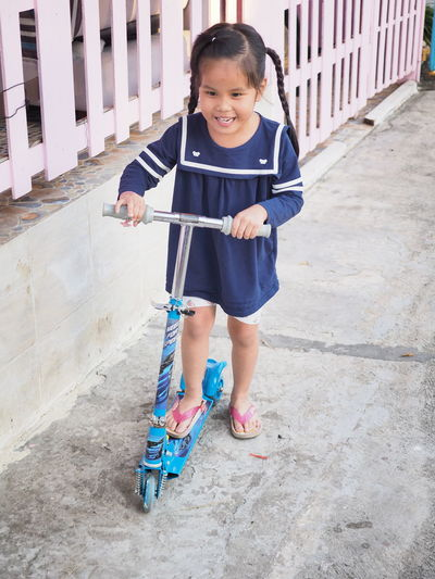 High angle view of smiling girl over push scooter on footpath