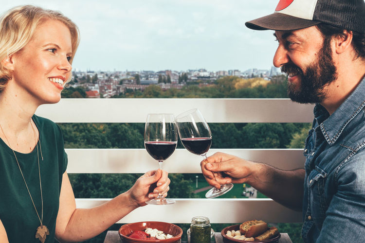 young couple dining on a terrace Couple Toasting Alcohol Bonding Close-up Day Drink Food Food And Drink Friendship Happiness Indoors  Lifestyles Men People Real People Red Wine Smiling Table Togetherness Two People Wine Wineglass Women
