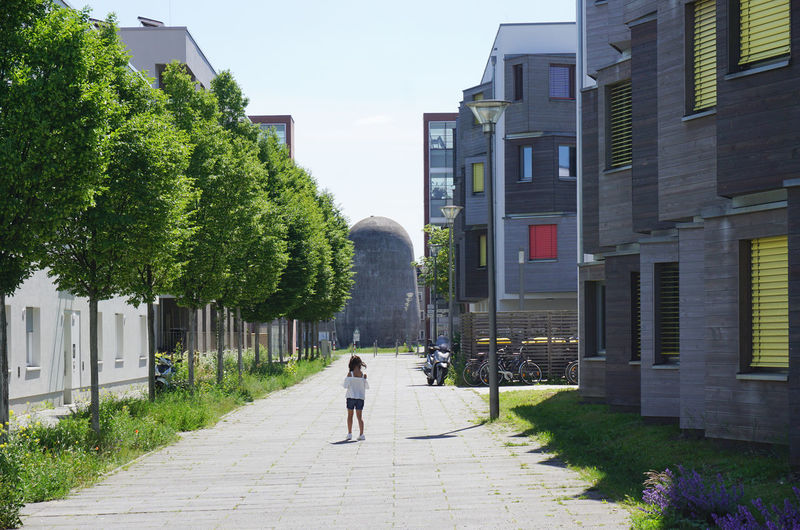 Rear view of man walking on footpath amidst buildings in city