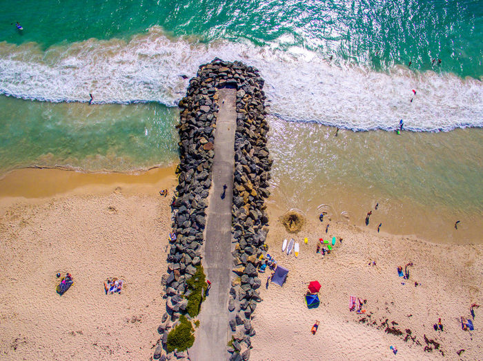 High angle view of people on pier and beach