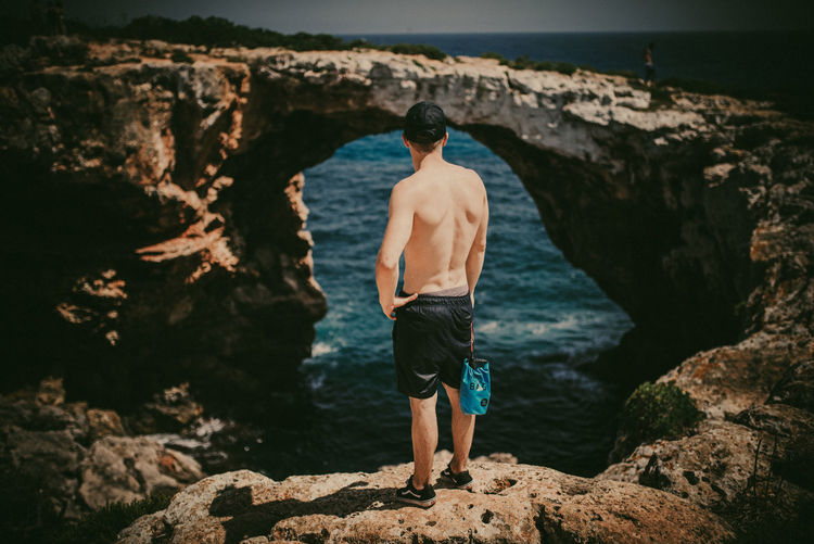 Rear view of shirtless man standing on rock by sea