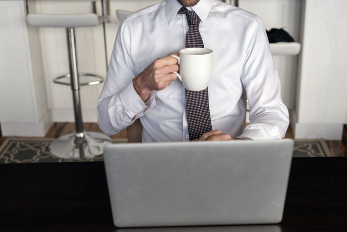 Headless male professional checking morning laptop computer while holding a cup of coffee. Adult Business Businessman Coffee Communication Computer Connection Cup Drinking Food And Drink Holding Indoors  Keyboard Laptop Management Occupation Office One Person Sitting Table Technology Telecommute White Shirt Wireless Technology Working