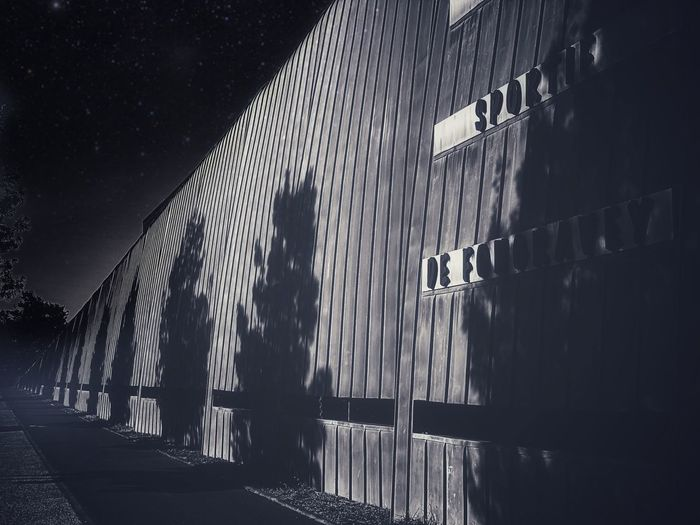 Shadow of person walking on footpath by building