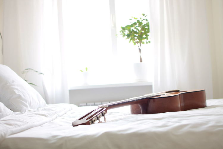 Acoustic guitar in bed at home