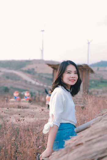 Portrait of beautiful woman standing on land against sky