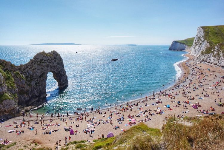 High angle view of people at durdle door beach against clear blue sky