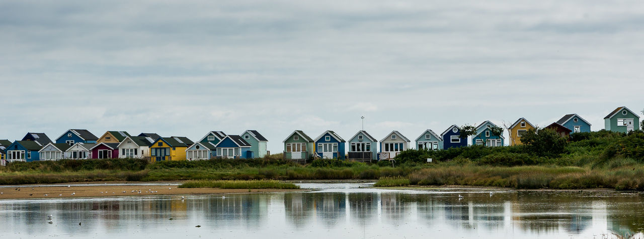 Colorful beach houses. Beachphotography Beachhouses Reflections Vintagedrama Beach Huts Seaside British Summer Serenity Peaceful View Mudeford Beach Hut Lake Newtalent