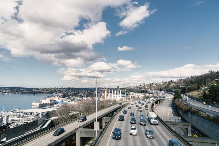 High angle view of cars moving on bridge against blue sky