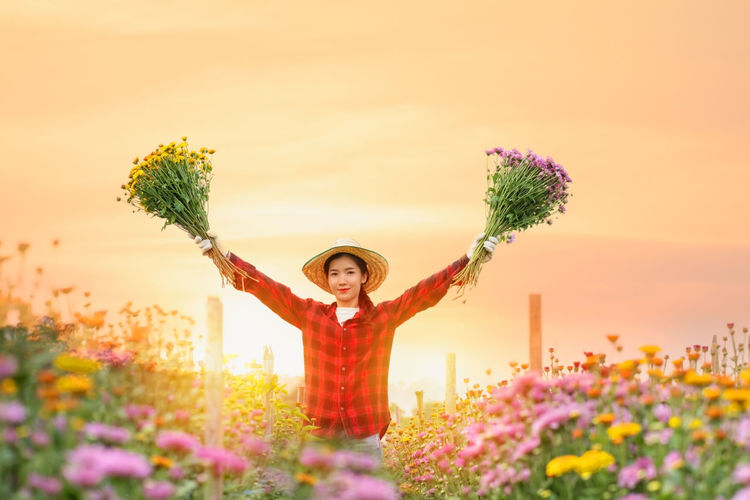Portrait of woman standing by flowering plants against sky during sunset