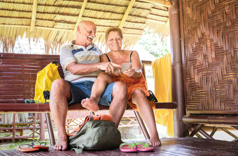 Smiling senior couple using phone while sitting on bench in hut