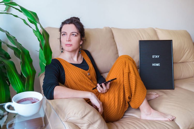 Woman with phone sitting on sofa at home