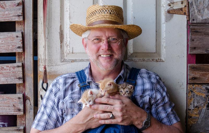 Portrait Of Smiling Man Holding Kittens Against Door