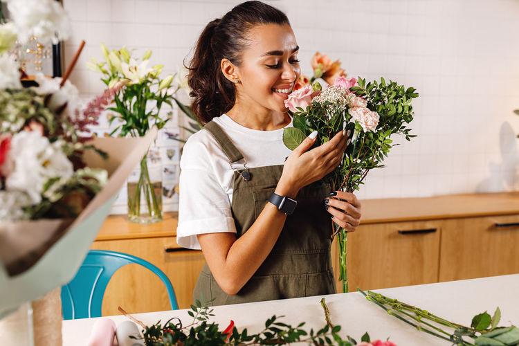 Smiling female florist holding bouquet in shop