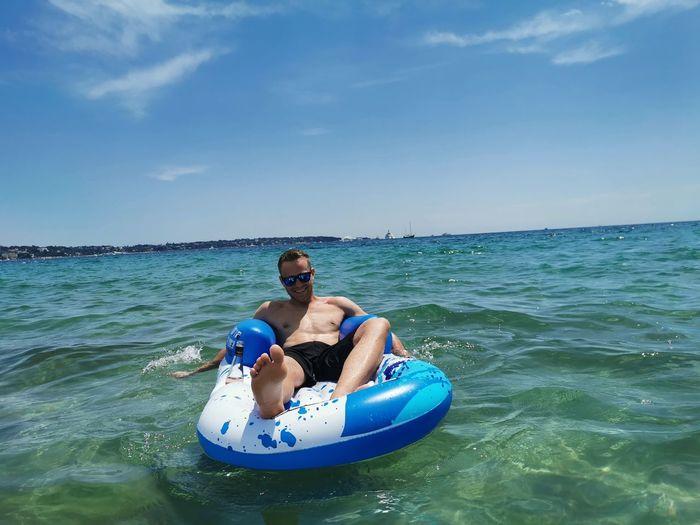 Man in pool raft at sea against blue sky