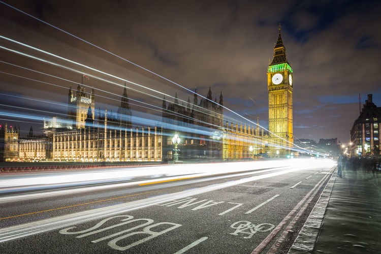 Light trails on road by big ben against sky in city at night