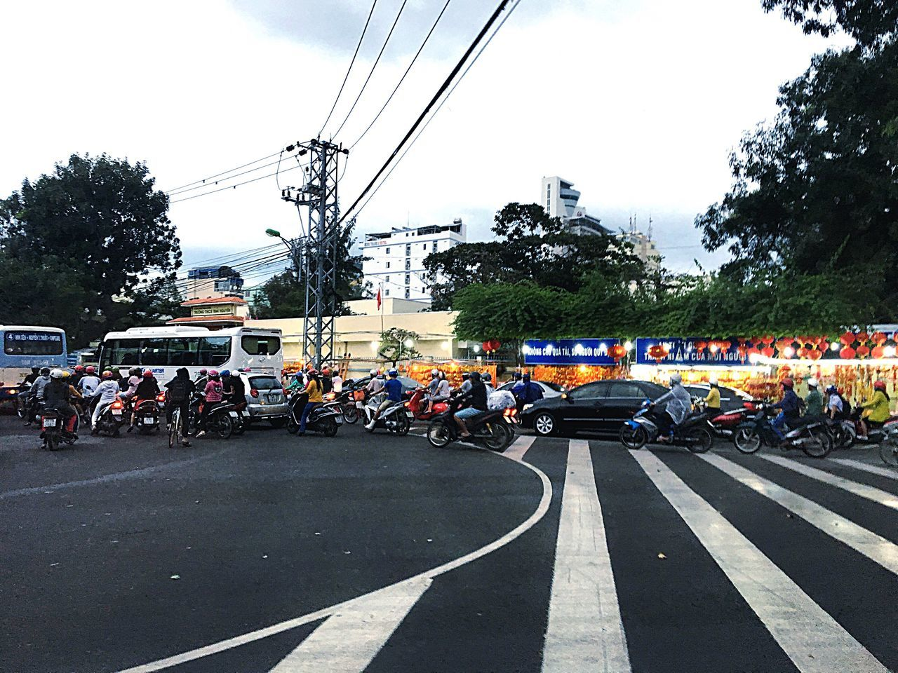 large group of people, real people, road, transportation, men, cable, day, tree, outdoors, sky, motorcycle, people, adult