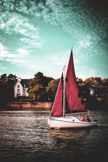 Sailboat on river by building against sky