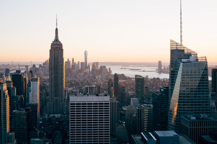High angle view of cityscape and empire state building against clear sky during sunset