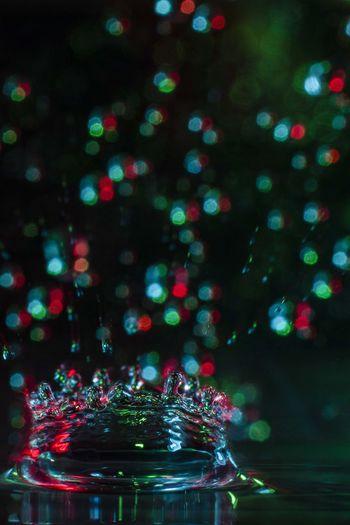 Close-up of splashing droplet against illuminated christmas lights