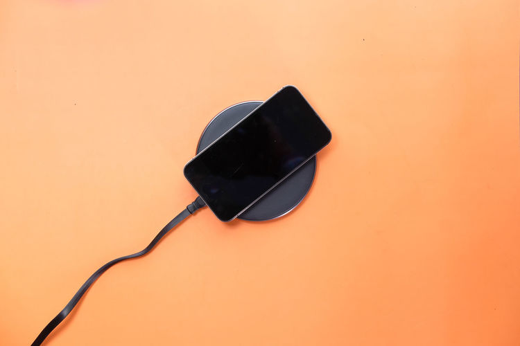 High angle view of smart phone against orange background