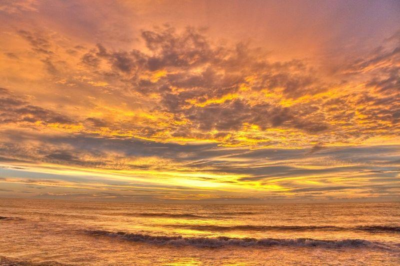 Sea under dramatic sky during sunrise