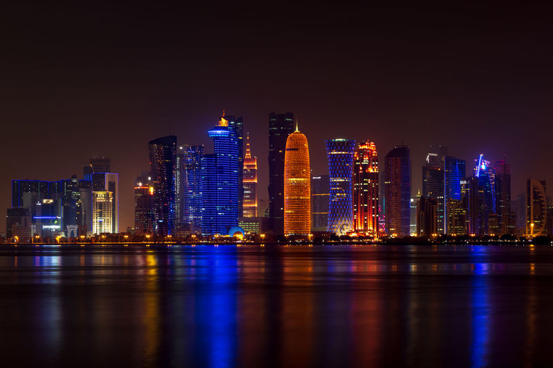 Coloful illuminated skyline of doha at night, qatar, middle east against dark sky