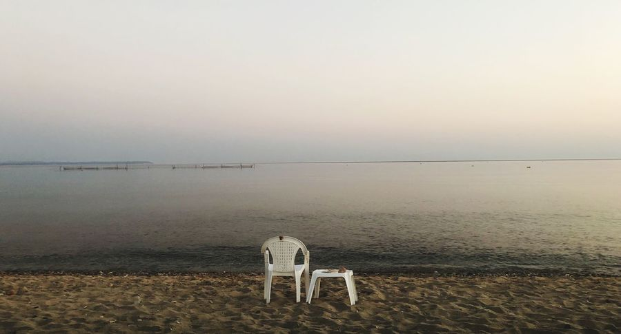 White chair and small table in a beach in an area in Greece Halkidiki Greece Sky Water Sea Beach Horizon Over Water Scenics - Nature Nature Beauty In Nature Tranquility Tranquil Scene No People Sunset Horizon Copy Space Clear Sky Land Dusk Day Outdoors