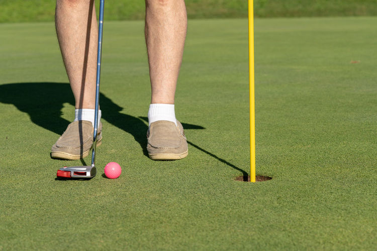 Man with putter and golf ball in pink color to on a well manicured putting green Feminine  Golf Golf Ball Grass Man Pink Ball Flag Golf Golf Course Golf Hole Golfer Grass Hole Legs Leisure Activity Mown Pink Color Putter Putting Putting Green Sport
