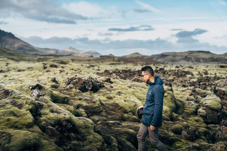 Photographer Hiking Through Rough Terrain In Iceland