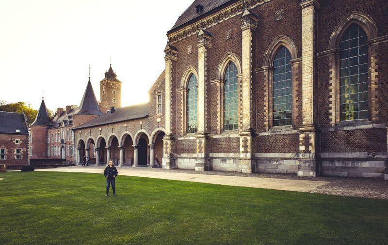Full length of boy standing on grass against church