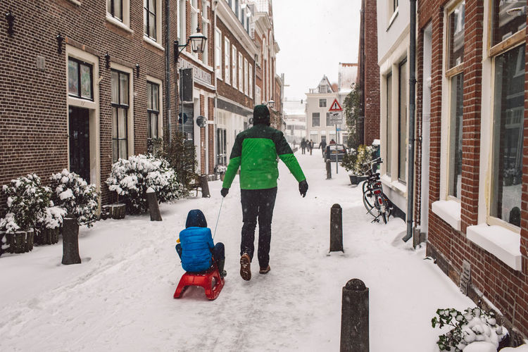 Rear view of child on snow covered buildings in city