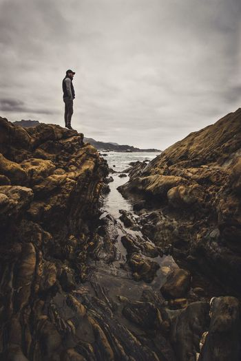 Man standing on cliff at beach against cloudy sky