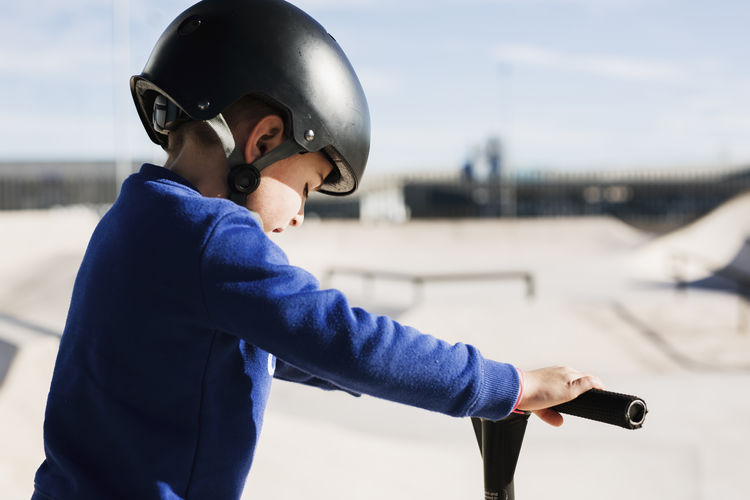 Side view of boy standing on motorcycle