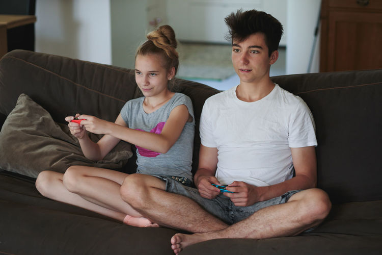 Concentrated young boy and girl playing video games sitting on sofa at home Children Family Gaming Home Relaxing Siblings Boy Casual Clothing Childhood Domestic Life Game Game Controller Girl Indoors  Leisure Activity Lifestyles Living Room Play Real People Relaxation Sitting Technology Teenager Two People Video