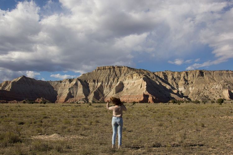 Full length rear view of woman standing on field by rocky mountains against cloudy sky at kodachrome basin state park
