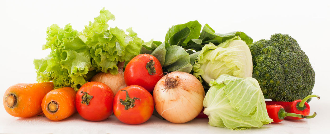 Fresh vegetables and tomatoes against white background