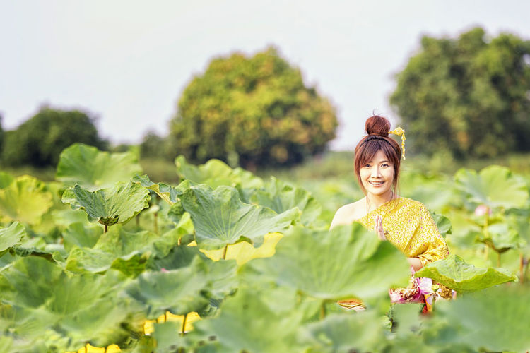 Portrait of young woman wearing traditional clothing standing amidst plants