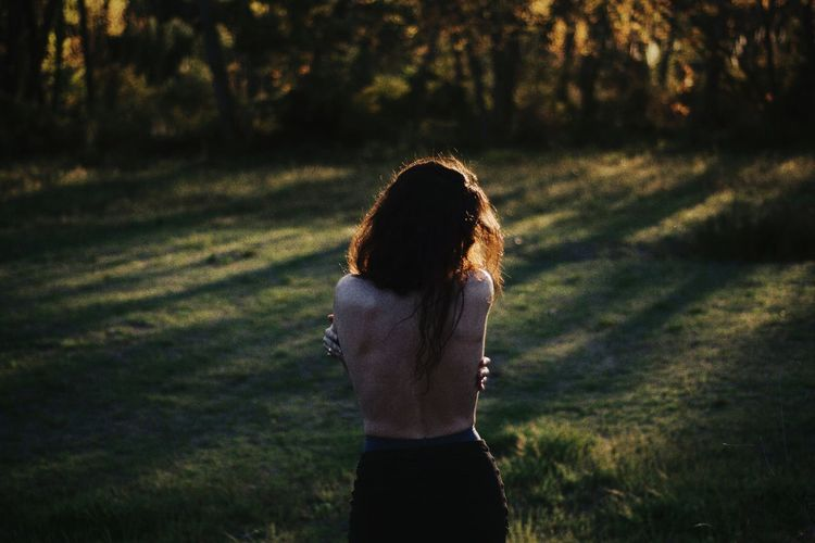 Rear View Of Shirtless Woman Standing On Grass Field In Forest